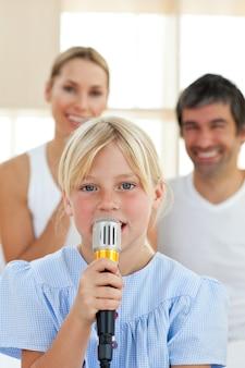Bambina adorabile che canta con un microfono
