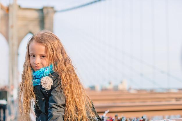 Bambina adorabile che si siede al ponte di brooklyn a new york