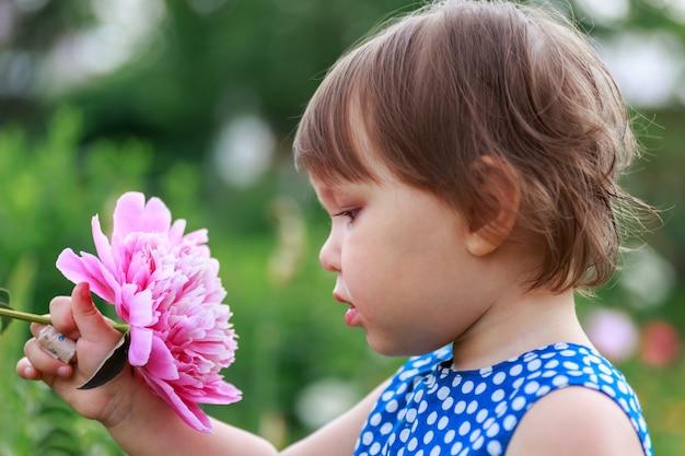 Bambina adorabile che fiuta i fiori viola