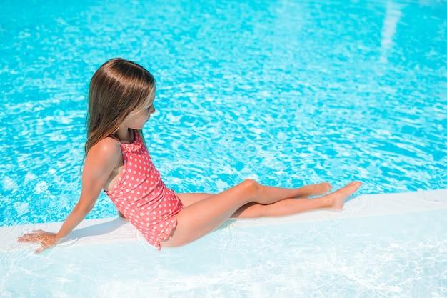 Nuoto adorabile della bambina alla piscina all'aperto
