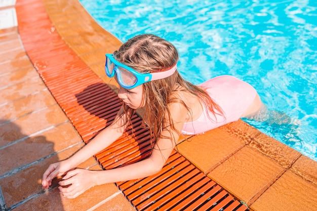Bambina adorabile che nuota alla piscina all'aperto