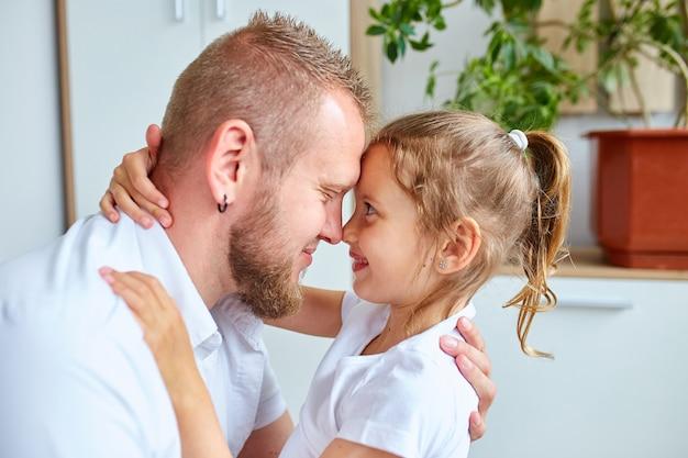 Adorabile bambina in abito bianco che abbraccia il padre amorevole che lo guarda con amore e tenerezza, padre e figlia che trascorrono del tempo a casa.