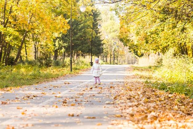 Adorabile bambina con foglie di autunno nel parco di bellezza