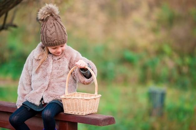 Bambina adorabile con un cestino nel giorno di autunno all'aperto