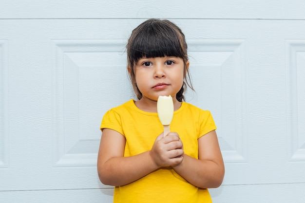 Adorabile bambina con i capelli neri che mangia il gelato, indossa una camicia gialla appoggiata a uno sfondo bianco