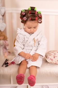La bambina adorabile con i bigodini dipinge le sue unghie. copia il comportamento della mamma. giovane fashionista. giornata della bellezza.