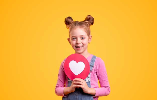 Bambina adorabile con i panini dei capelli svegli che sorridono e che dimostrano il segno del cuore