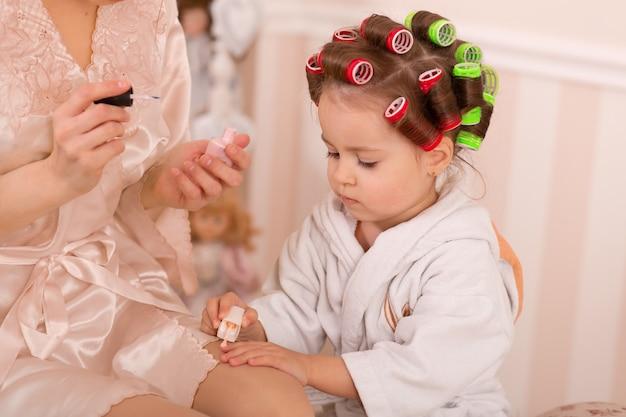 Adorabile bambina con sua madre in bigodini dipinge le unghie. copia il comportamento della mamma. la mamma insegna a sua figlia a prendersi cura di se stessa. giornata della bellezza.