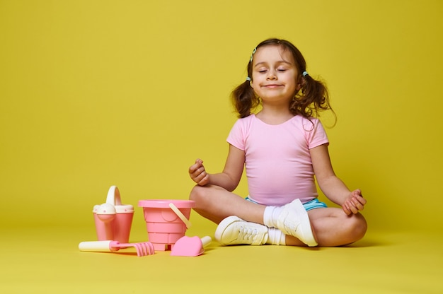 Adorabile bambina con coda di cavallo che indossa abiti estivi meditando con gli occhi chiusi, seduto vicino a set di giocattoli da spiaggia su giallo con copia spazio.