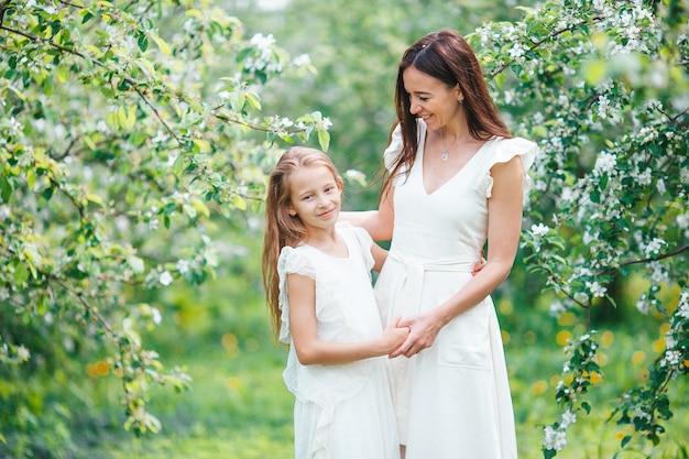 Adorabile bambina con la giovane madre nel giardino di ciliegio in fiore in una bella giornata di primavera