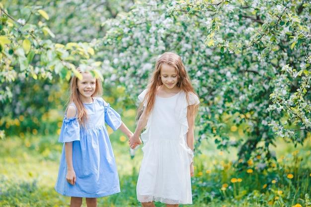Bambine adorabili nel giardino di melo in fiore il giorno di primavera