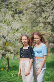 Adorabili bambine nel giardino di melo in fiore il giorno di primavera