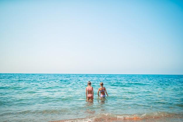 Adorabili bambine divertendosi sulla spiaggia