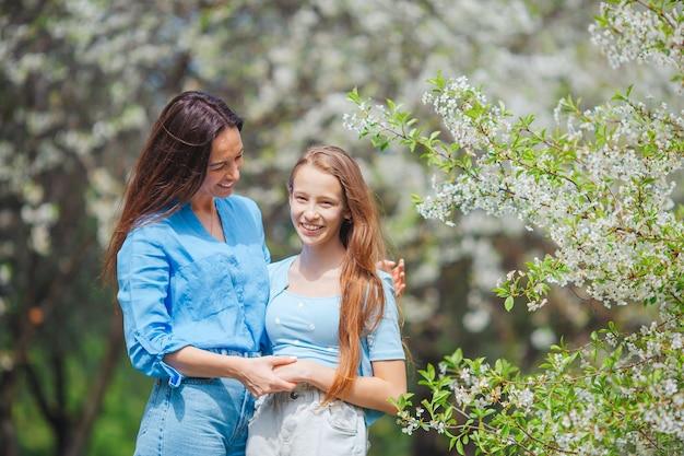 Adorabili bambine con una giovane madre in un giardino di ciliegi in fiore in una bella giornata di primavera