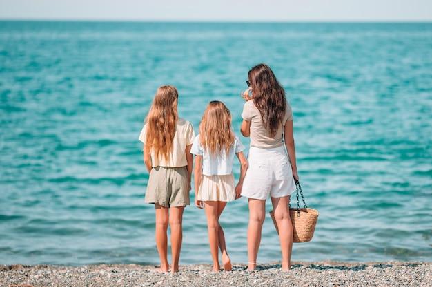 Adorabili bambine e giovane madre sulla spiaggia bianca tropicale