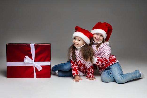 Adorabili sorelline che portano il cappello rosso della santa che si abbracciano sul pavimento con un grande regalo di natale in carta rossa e muro grigio bowon bianco.