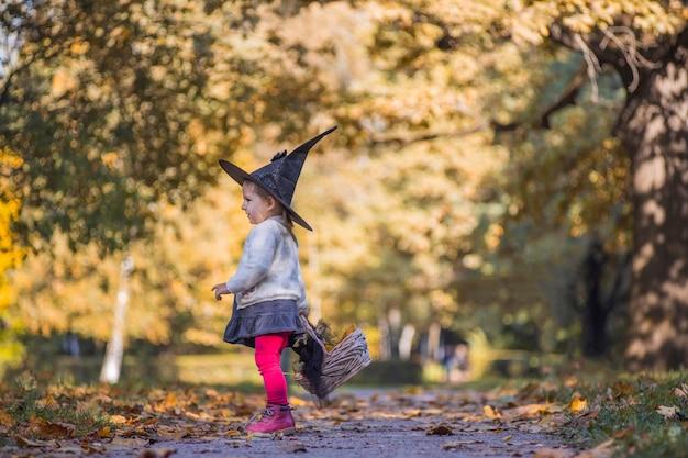 Adorabile bambina in autunno parco ragazza in costume da strega e cappello nero cosplay halloween