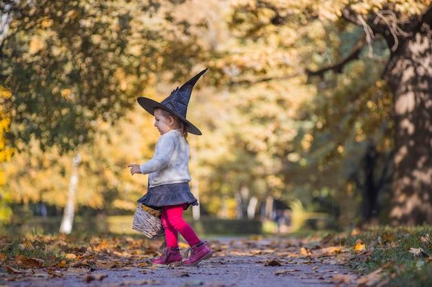 Adorabile bambina che cammina nel parco autunnale. ragazza in costume da strega e cappello nero cosplay costume di halloween. festa di halloween