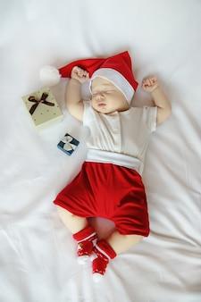 Adorabile neonato in costume di babbo natale e scatole regalo di natale dorme dolcemente sul lenzuolo bianco