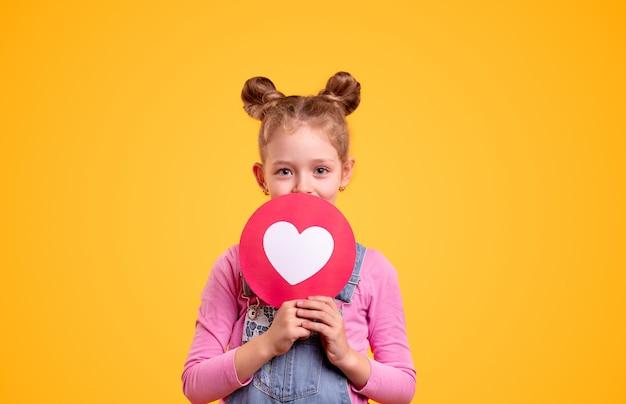 Adorabile bambina positiva con graziosi panini per capelli che mostrano i social media del cuore rosso come l'icona