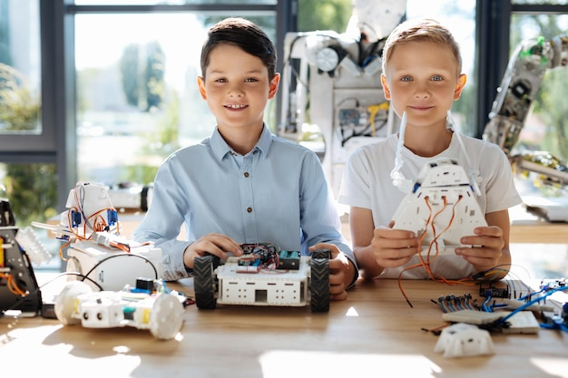 Adorabili bambini pre-adolescenti che ispezionano l'officina del veicolo robotico