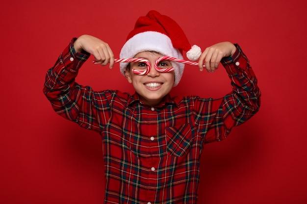 Adorabile ragazzo preteen in cappello di babbo natale e camicia a quadri sorride guardando la telecamera attraverso i bastoncini di zucchero dolci di natale, tenendoli imitando gli occhiali, posando su sfondo rosso con spazio copia per l'annuncio