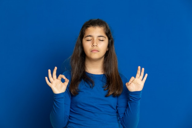 Ragazza adorabile del preteen con la maglia blu che gesturing sopra la parete blu Foto Premium