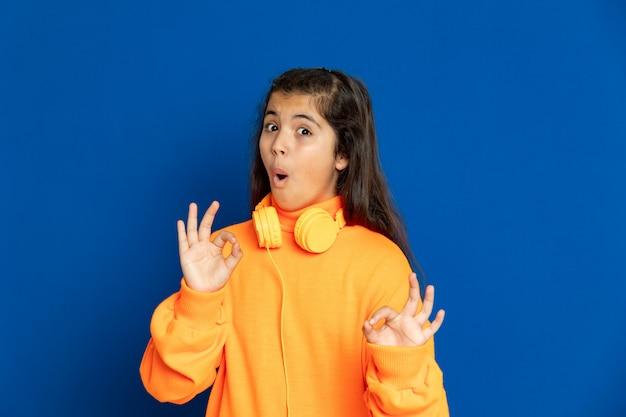 Ragazza adorabile del preteen con la maglia gialla che gesturing sopra la parete blu Foto Premium