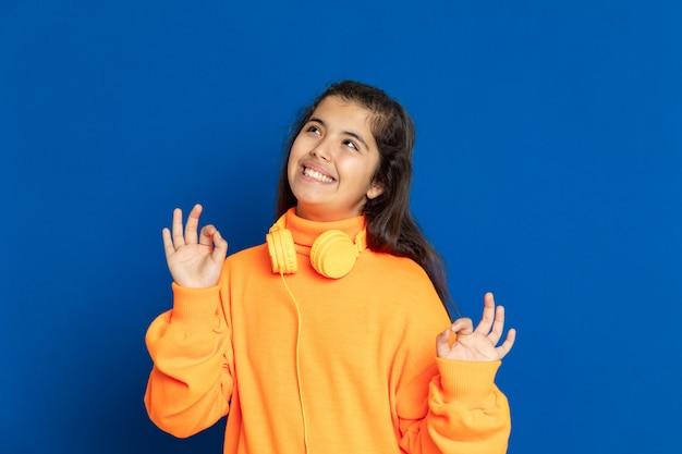 Ragazza adorabile del preteen con la maglia gialla che gesturing sopra la parete blu