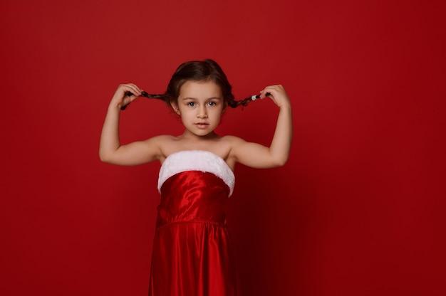 Adorabile bambina di 4 anni carina, bambino carino in abiti di babbo natale posa tenendo le trecce, guarda la macchina fotografica. isolato su sfondo rosso con copia spazio per la pubblicità di natale e capodanno