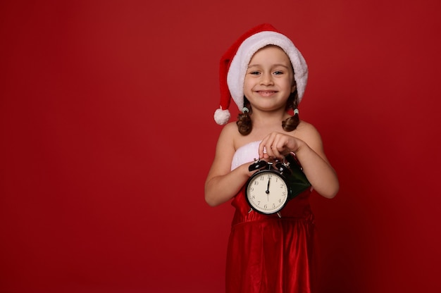 Adorabile bella bambina vestita in costume di carnevale di babbo natale posa con sveglia con mezzanotte sul quadrante, guardando la fotocamera, su sfondo di colore rosso con copia spazio per l'annuncio di natale