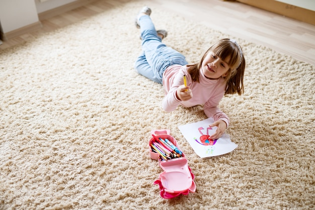 Ragazza abbastanza piccola adorabile del bambino che attinge carta con i pastelli di legno mentre trovandosi sul tappeto nella sua stanza.