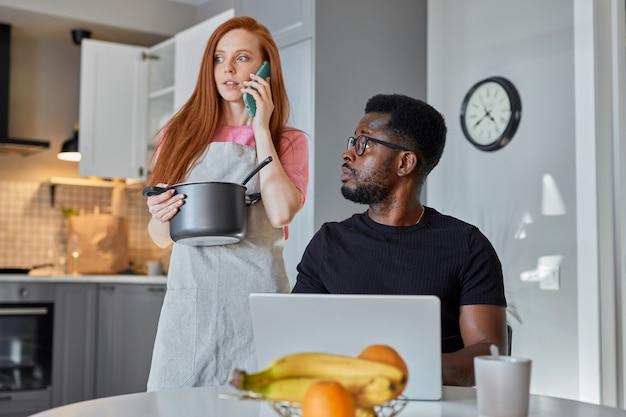 Donna adorabile della testarossa sostiene il marito che lavora