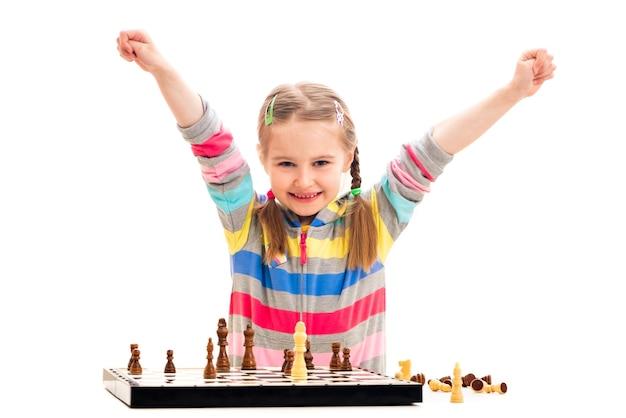 Adorabile ragazza in età scolare si sente estremamente felice di vincere a scacchi isolato su uno sfondo bianco