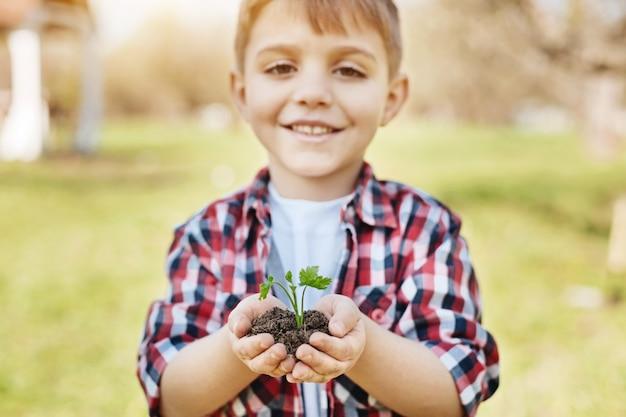 Adorabile bambino in età scolare che sorride ampiamente mentre tiene un giovane germoglio fresco e guarda in avanti