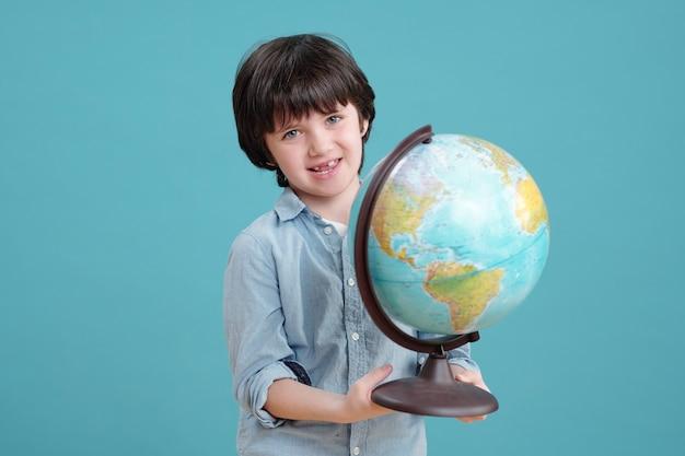 Adorabile scolaro o bambino in età prescolare con il globo che ti guarda