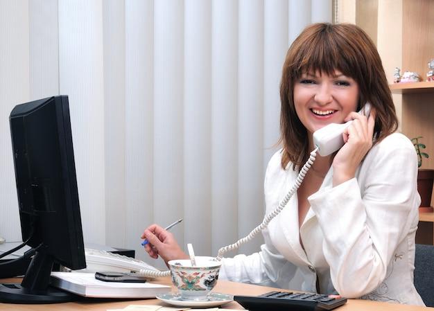 Donna castana bianca caucasica sorridente adorabile che parla sul telefono alla scrivania durante il tempo di pausa.