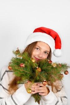 Adorabile ragazza sorridente con il cappello di babbo natale rosso