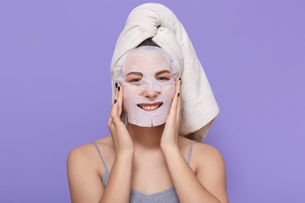 Adorabile signora sorridente avvolta in un asciugamano in posa isolato su lilla, utilizzando la maschera in tessuto per le procedure di bellezza