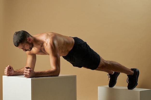 Adorabile sportivo con muscoli del busto che sviluppano forza nella stanza al chiuso