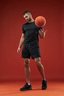 Adorabile forte atleta muscoloso in posa davanti alla telecamera con il basket in mano al chiuso