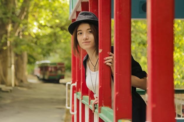 Adorabile ragazza adolescente con abiti neri in un colorato treno per bambini guardando davanti e sorridente