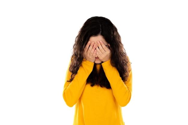 Adorabile ragazza adolescente con maglione giallo isolato su un muro bianco