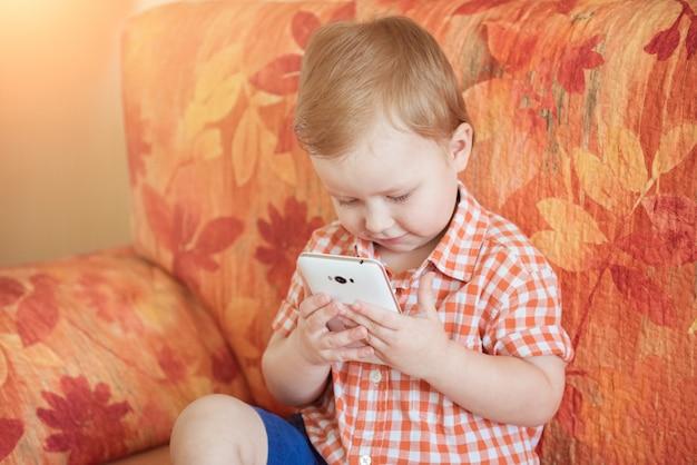 Ragazzo adorabile del bambino che si siede sul sofà nel salone e che gioca con lo smartphone.