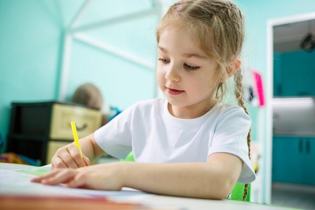 Adorabile ragazza del bambino che disegna con le matite a casa seduta al tavolo. bambino creativo seduto in una stanza che impara a disegnare. ragazza del bambino che fa i compiti a casa.