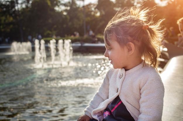 Adorabile bambina guarda lo stagno con fontane nel parco in una giornata di sole. passeggiata in famiglia nel fine settimana. passare del tempo con i bambini. focus artistico