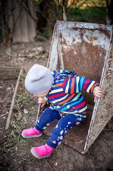 Adorabile bambina seduta in carriola in fattoria agricoltura e giardinaggio per bambini piccoli