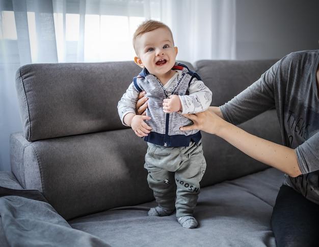 Adorabile bambino in piedi sul divano con l'aiuto di sua madre.