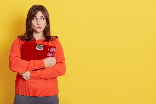 Donna adorabile che si sente perplessa e confusa, dubita, appesantisce, indossa un maglione arancione casual