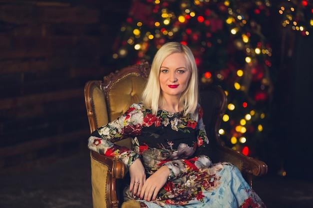 Adorabile giovane donna bionda si siede sul pavimento accanto al caminetto in un luminoso abito floreale su un albero di natale, si appoggia su una poltrona.